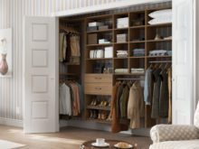 Reach in Closet with Closet Rods and Light Brown Drawers and Shelving