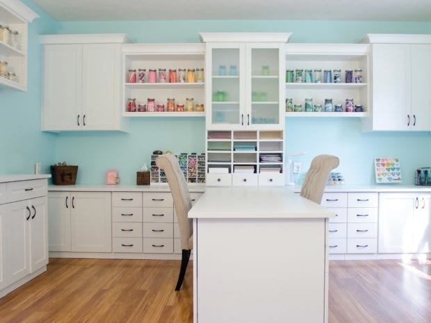 White Themed Craft Room With Glass Fronted Display Cabinet Shelving Cubbies and Work Space
