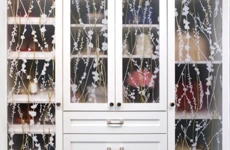 Close up of White Shaker Cabinet with Drawers and Glass Decoratively Etched Doors and