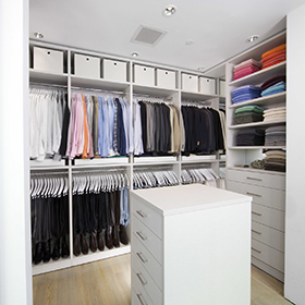 California Closets Walk in closet in white finish with large hanging racks and island counters