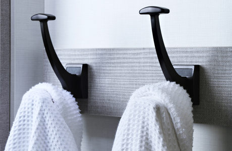 black towel and coat hangers with light gray backing board
