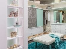 White Themed Walk in Closet with Cabinets Lighted Shelving and Vanity Turquoise and Etched Glass Accent Doors and Stand Alone Bench Seating