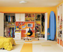 White Reach in Children's Closet With Shelves Closet Rods Metal Baskets Built in Desk and Yellow Accents