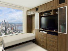 Dark Brown Built in Cabinets With Entertainment Center Murphy Bed and Shelving With Glass Doors and Built in Lighting