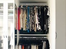 White Walk in Closet Close Up of Hanging Clothes and Cabinets with Glass Doors
