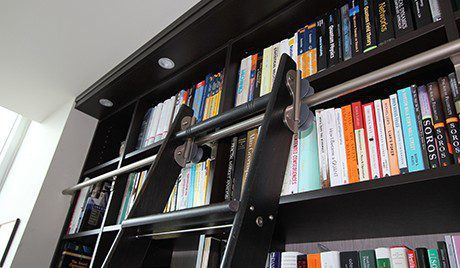 Close up of Black Library Shelving with Built in Lighting and Rolling Library Latter