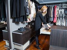 Dark Brown Walk in Closet With Drawers Shelving and Hanging Clothes