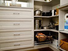 Close up of White Wood Grain Pantry Storage With Drawers Shelving and Pull out Metal baskets