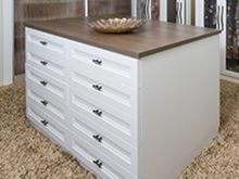 Close Up of Walk in Closet White Stand Alone Dresser with Dark Brown Wood Grain Top