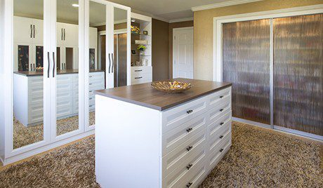 White Walkin Closet with Mirrored Wardrobe Doors Shelving with Frosted Glass Sliding Doors and Stand Alone Dresser with Dark Brown Wood Grain Top