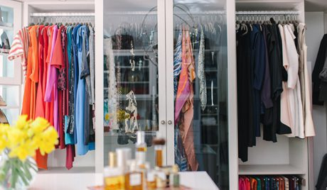 Close Up of High Gloss Walk in Closet With Glass Wardrobe Doors and Organized Hanging Clothes