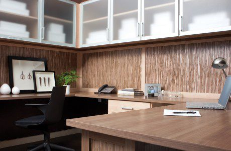 Light Wood Office with Wood Textued Back Panels Built in Wrap Around Desk and Frosted Glass Cabinet Doors with White Trim