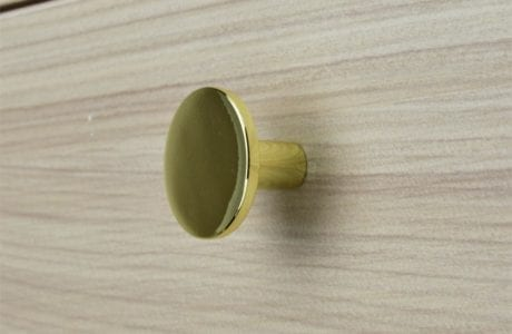 Close Up Image of Natural Wood Grain Dresser Drawer with Brass Drawer Knob