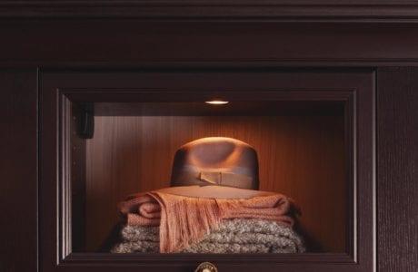 Close Up of Dark Brown Hard Wood Closet Display Cabinet With Glass Door Built in Lighting and Decorative Bronze Handle