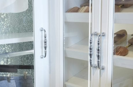 Close Up of White Closet Doors With Glass Inlays and Polished Metal Handles