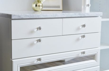 Close up of White Dresser wtih Clear Drawer Knobs Inlayed Decorative Mirrors and Granite Counter Top