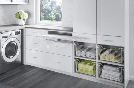 White Themed Laundry Room with Shelving Cabinets Counter Tops and Pull Out Ironing Board and Wicker and Metal Baskets