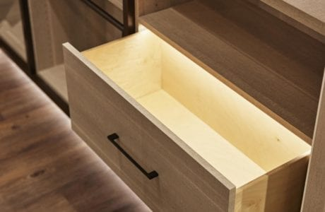 Close Up of Light Wood Closet Dresser Drawers with Black Handles and Built in Lighting