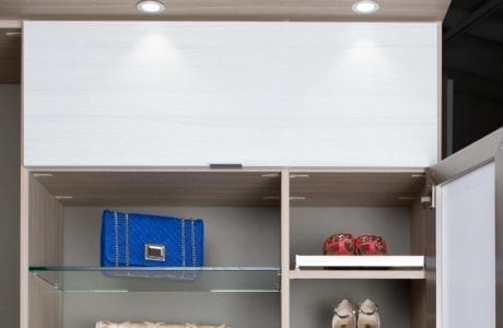 Close Up of Light Grey Wood Grain Closet Storage with Glass Shelves Shoe Racks White Cabinet Door and Built in Puck Lighting