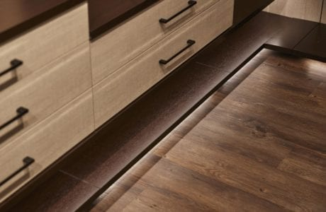 Close Up Image of Dark Brown Wood Grain CLoset with Built in Toe Kick Lighting
