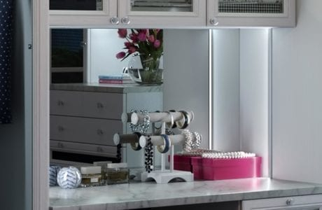Close Up image of Closet Vanity Space with Glass Door Cabinets Granite Counter Top Built in Lighting and Large Mirror