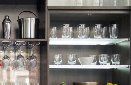 Close Up of Dark Grey Bar with Cabinets Wine Glass Hanging Racks and Frosted Glass Shelves