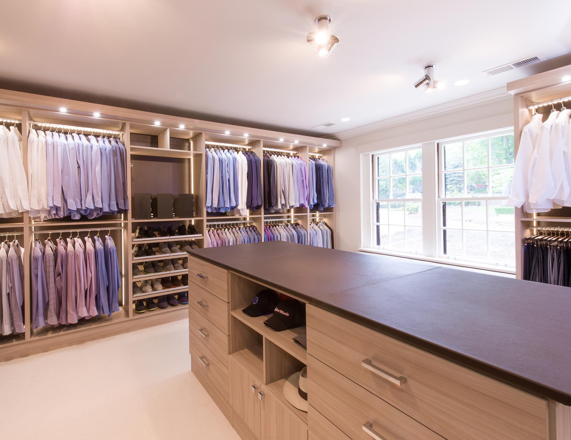 Natural wood walk in closet with closet rods drawers cabinets shoe racks vanity mirror and built