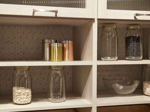 Close Up of White Wood Grain Pantry Storage with Shelving Decorative White back Panels and Cabinets with Frosted Glass Doors