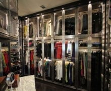 Black and Grey Walk in Closet wiht Glass Display Cabinets and Shelves with Metal Trim and Built in Lighting