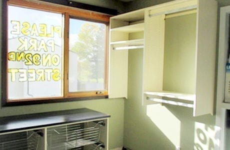 White Built in Storage with Shelving Closet Rods Slide Out Metal Baskets and Black Counter Tops