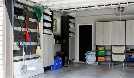 Client Stories Redesigned Garage Storage Space with Dark Brown Hanging Rack and Shelving and Light Wood Cabinets