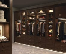 Walk in Closet with Dark Wood Cabinets Shoe Racks Closet Rods and Built in Lighting