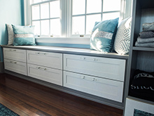 Cabinet storage underneath a window seat with decorative pillows