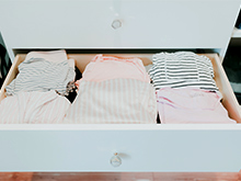 Folded shirts in a white front drawer pulled out