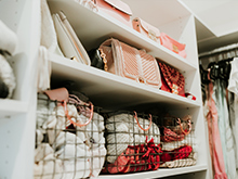 White shelving display purses and wire baskets hold folded shirts