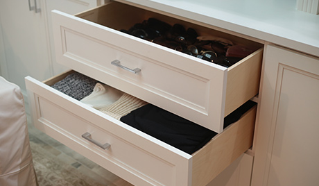 Light tan drawers out to reveal folded shirts