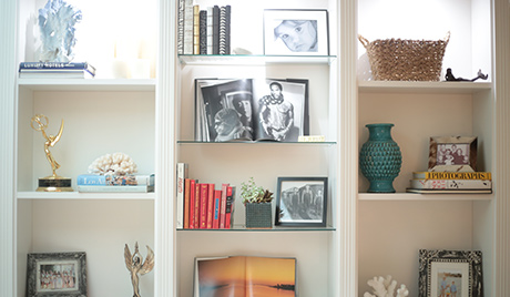 Front view of white shelving displaying photographs and trophies for TV personality Charissa Thompson