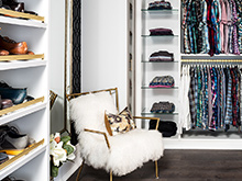 A gold chair with fluffy white backing sits in front of shoe shelving with gold fences