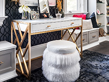White shaggy cushion sits in front of a white and gold vanity