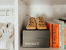 Baby shoes sitting on top of a box on white shelving