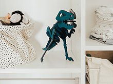 White shelving holding a dark green toy dinosaur skeleton