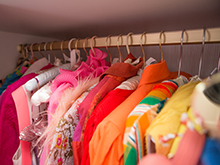 Close Up Image of Gold Closet Rod with Colorful Hanging Clothes