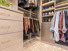 Men's shirts and accessories organized in light tan custom shelving and drawers