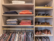 Matte brass shoe fences and hanging poles in an organized man's custom closet