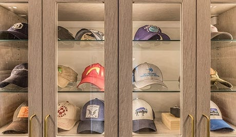Cabinets with clear glass fronts housing baseball caps