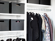 Black storage boxes sit in white custom shelving