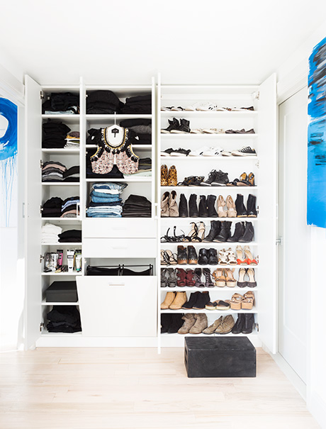 White shelving and folded clothes and organized shoes