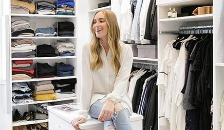 California Closets client Kimberly Lapides sitting and smiling in her new walk in closet