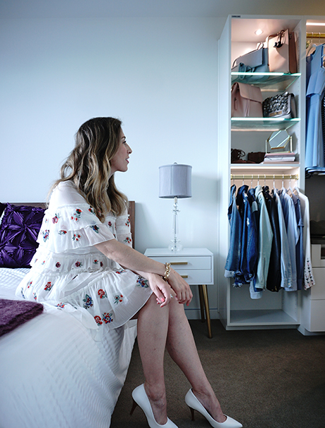 California Closets Client Story Becky Kung Sitting On Her Bed Looking At New Closet