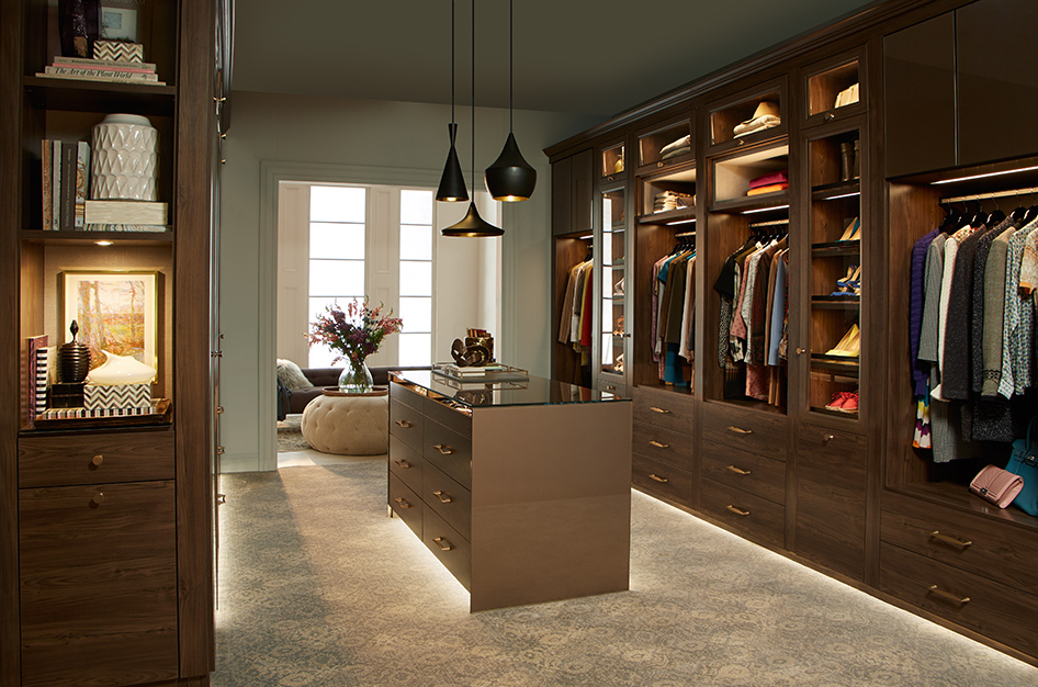 Sophisticated bedroom walk in closet by California Closets